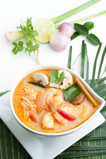 Thai shrimp tom yum soup bowl close up with noodles.