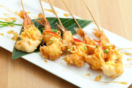 Tempura jumbo shrimp skewers on a white plate.