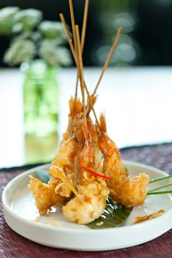 Tempura jumbo shrimp skewers on a white plate standing up vertically.