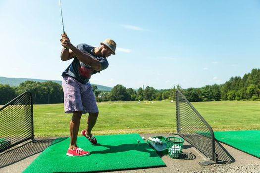 Athletic golfer swinging at the driving range dressed in casual attire.