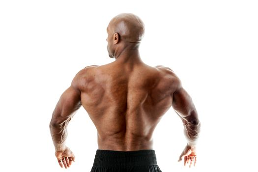 Toned and ripped lean muscle fitness man standing in front of a white background. Shallow depth of field.