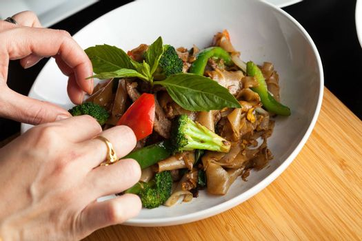 Food stylist grooms a dish by adding sweet basil garnish to the traditional thai dish Pad Kee Mao drunken noodle.