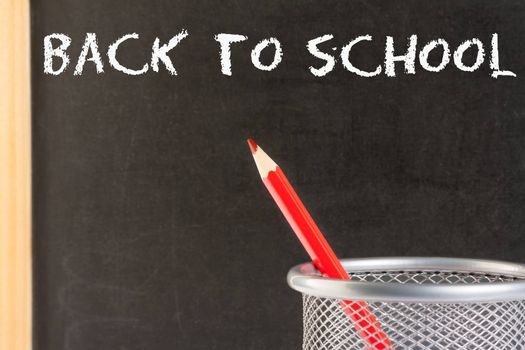 back to school, red pencil in container against blackboard