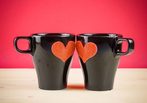 valentine day series, cups of milk with decorative heart on wood table and red background background with space for text