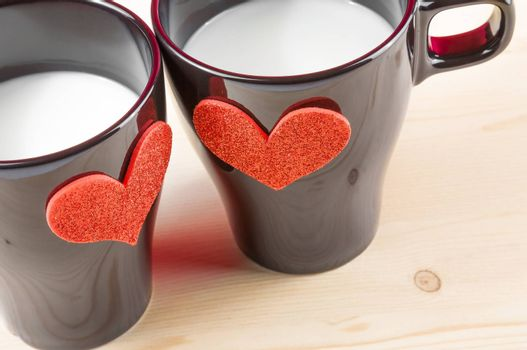 cups of milk with decorative hearts on wood table with space for text, concept of valentine day