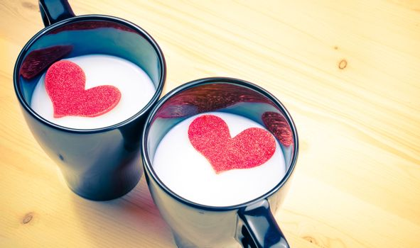 vintage style of cup of milk with decorative hearts on wood table with space for text, concept of valentine day