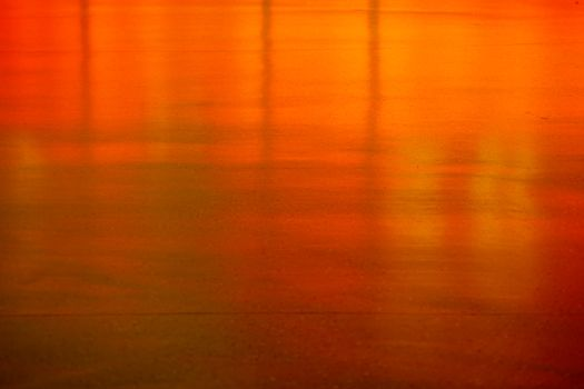 An orange and neon reflective smooth floor in front of a bar.