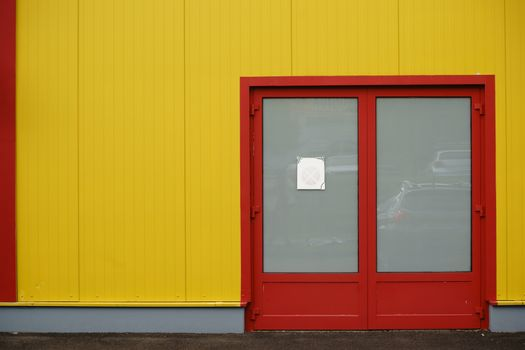 A colorful and striking sidewall of a shopping center with a side entrance, and strong bright color.