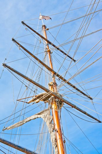 upwards view of a ship's masts on blue sky