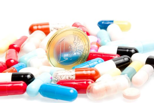 euro coins in the center of medical pills on white background