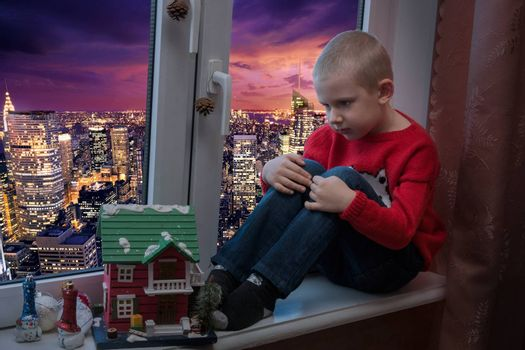 The photo depicts a boy on a windowsill