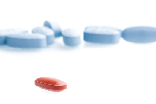 a single red medical pill in front of a lot of blue medical pills in laboratory on white table