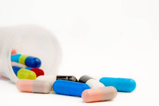 closeup of colored pills with unfocused bottle on white background