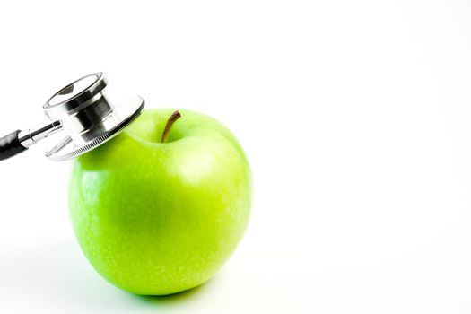 detail of medical stethoscope and apple on a white background with space for text