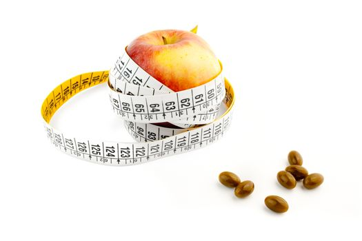 detail of pills and a apple with a measuring tape