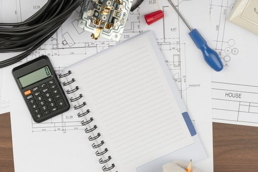 Man writing in copybook with calculator
