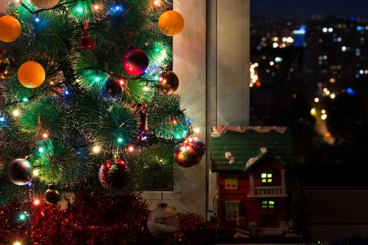 The photograph shows a house with a Christmas tree