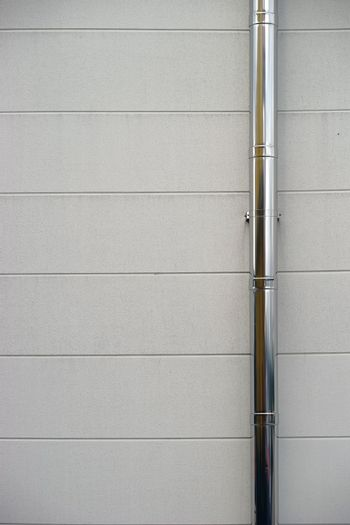 A shiny stainless steel gutter on the wall of a building.