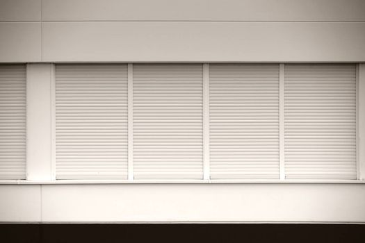 A number of modern windows of a business building with closed blinds.