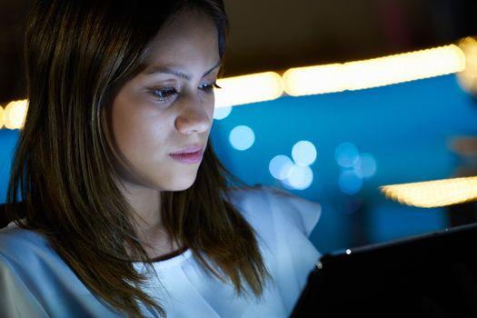 Latina Teenager Using Tablet PC Indoor At Night