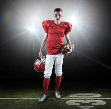 Composite image of a serious american football player taking his helmet on her hand looking at camer