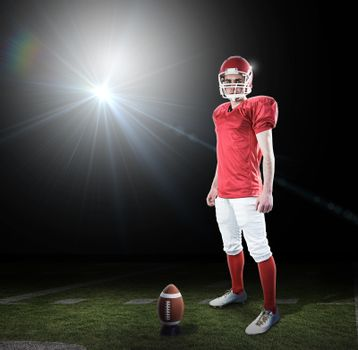 Composite image of a serious american football player taking his helmet looking at camera