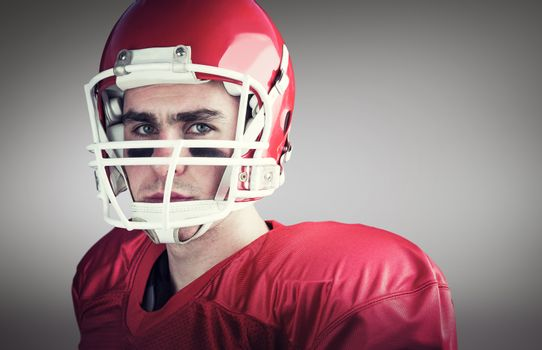 Composite image of portrait of a serious american football player taking his helmet looking at camer
