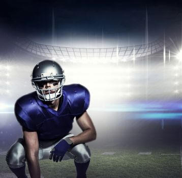 Composite image of american football player in uniform crouching