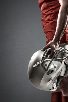 American football player holding helmet against grey