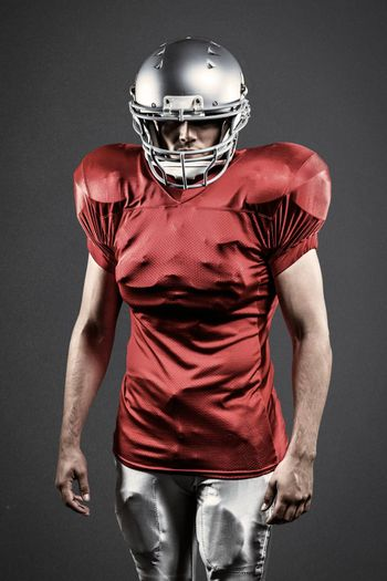 Confident American football player against grey