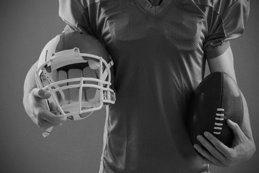 Composite image of american football player holding a helmet and ball