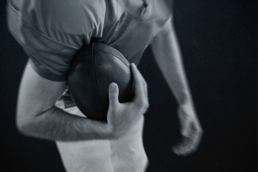 Composite image of american football player taking a ball on her hand