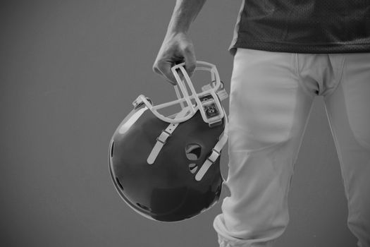 Composite image of an american football player taking his helmet on hand
