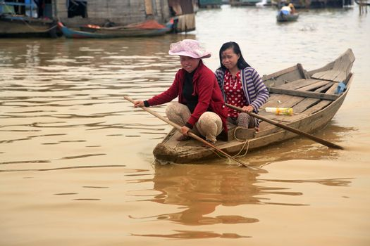 SIEM REAP, CAMBODIA - APRIL 06, 2014: A mother and daughter on a floating village on Tonle Sap lake in Siem Reap, Cambodia on april 06, 2014.