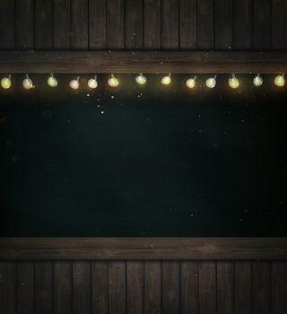 Christmas holiday lights on wooden blackboard