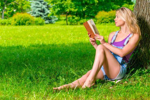 beautiful woman reading a romance sitting near a tree