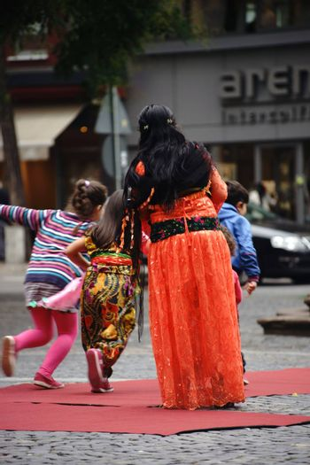 Mainz, Germany - September 25, 2015: Three Kurdish children playing in front of a Kurdish woman in a traditional costume at an event of the Intercultural Weeks on 25 September 25, 2015 in Mainz.