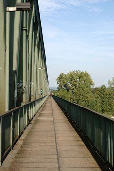 A bike and pedestrian path on the side of a railroad bridge.