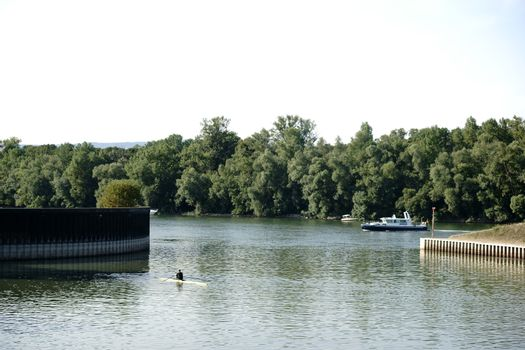 A sports rowing boat and a small boat on a river corridor along the Rhine.