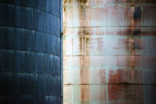 Two different metal surfaces of two water tanks in contrast to each other.