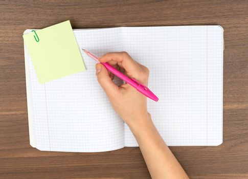 Open copybook with writing hand on table, top view
