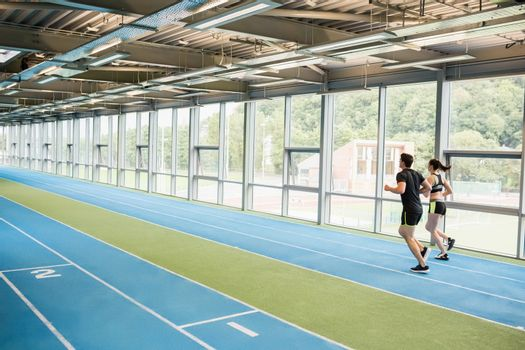 Couple running on the indoor track