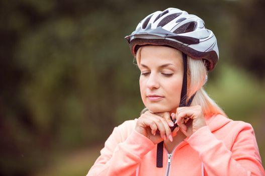 Woman fastening her bike helmet
