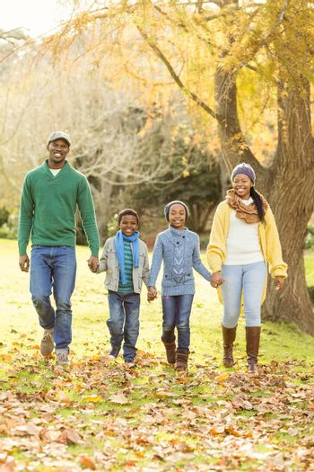 Portrait of a young smiling family walking on an autumns day