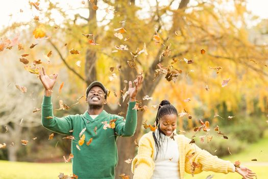 Portrait of a young couple throwing leaves around on an autumns day