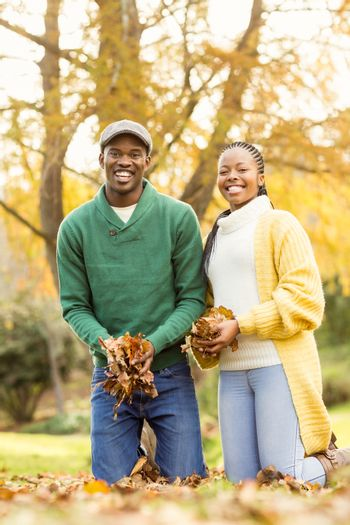 Portrait of a young couple holding leaves on an autumns day