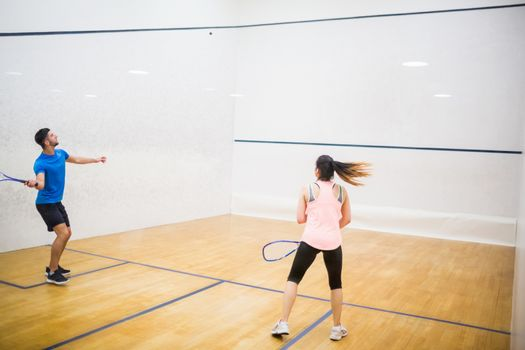 Competitive couple playing squash together