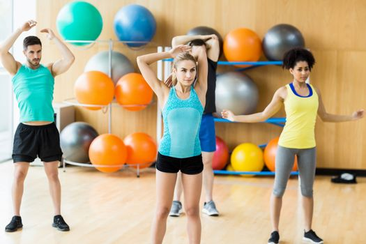 Fitness class exercising in the studio at the gym