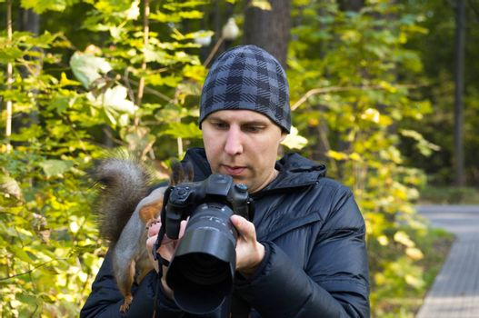 The photograph depicts a male photographer with a squirrel