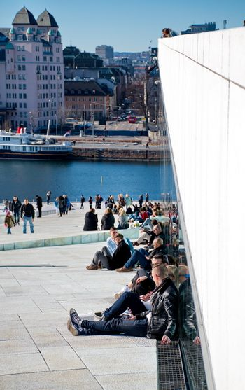 OSLO - MARCH 21: People hanging around in Opera house in Oslo. The building is designed by Snohetta company
